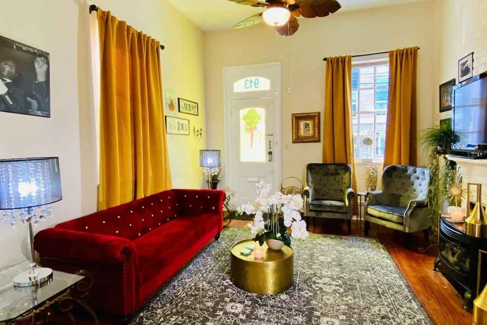 Living room with jeweled toned upholstery on couch and curtains in vacation rental in New Orleans