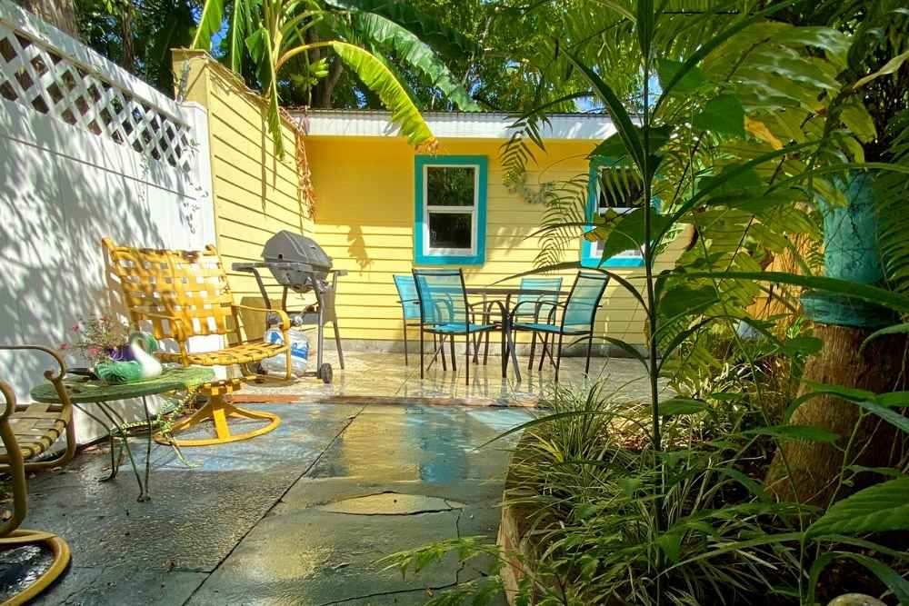 Courtyard seating area among lush green plants with vibrant colored outdoor furniture in vacation rental in New Orleans Louisiana