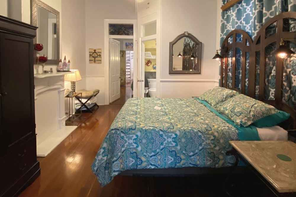 Cozy bedroom with multi colored bedding, mirror, night stand, and fireplace in vacation rental in New Orleans, Louisiana
